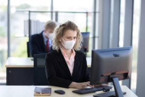 Business woman with curly blonde hair wearing a mask sitting in office, Concept,contagious disease, coronavirus.